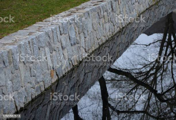 Photo of The stone-clad retaining walls of the river pond reservoir or dock are inaccessible to humans. the animals find it difficult to reach the water through the fortified granite walls. it is a trap