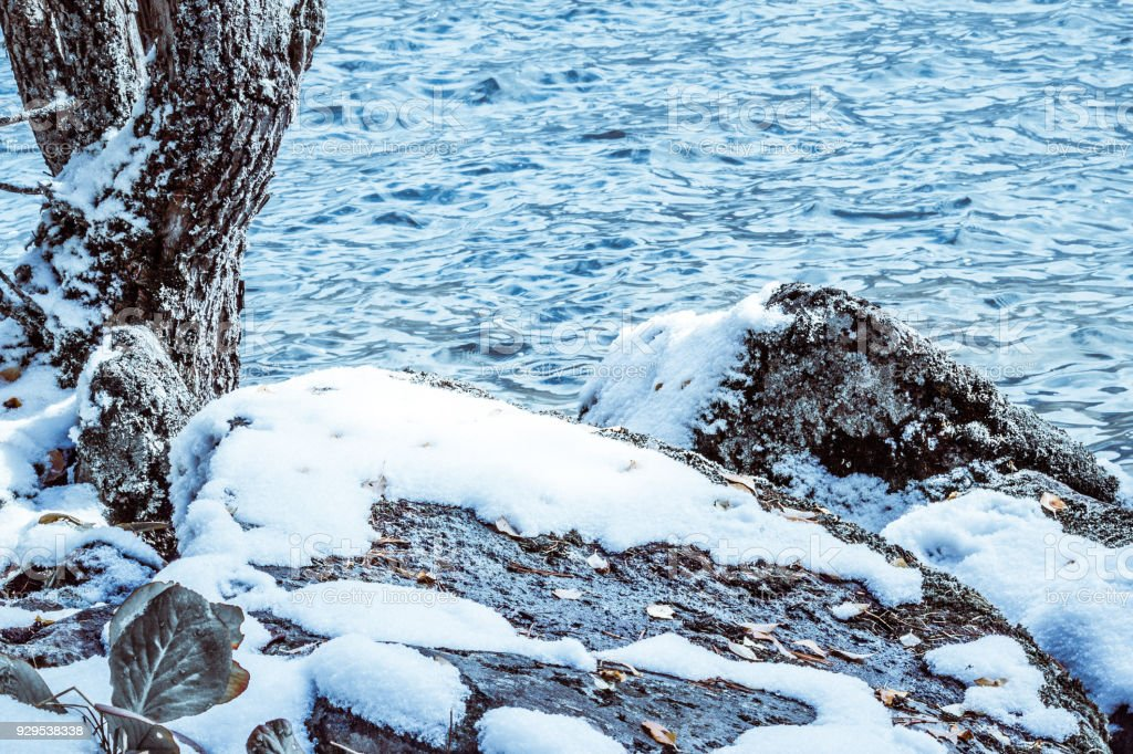 The stones and the wood under snow on a background of lake stock photo