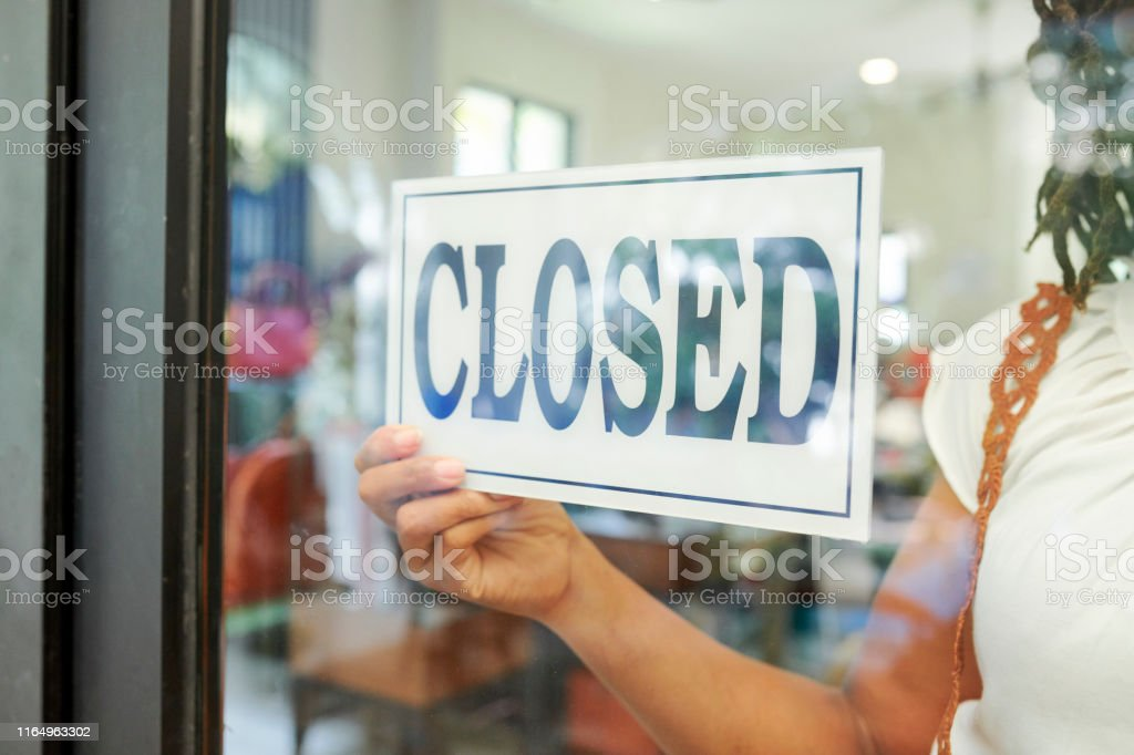 Close-up of saleswoman hanging the Closed sign on glass door and...