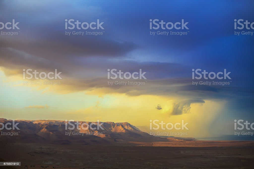The storm over mountain Masada in Israel. The dramatic landscape, dark blue sky above the mountain. royalty-free stock photo