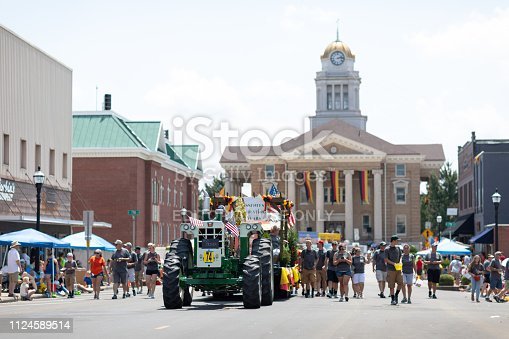 Jasper, Indiana, USA - August 5, 2018: The Strassenfest Parade, Man driving an old tractor, pulling a trailer with people