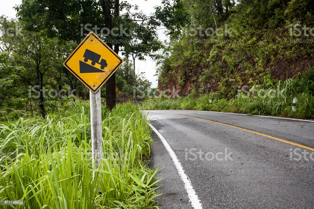 The street sign down hill warning on the mountain road stock photo