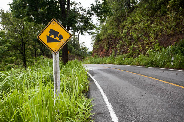The street sign down hill warning on the mountain road The street sign down hill warning on the mountain road steep stock pictures, royalty-free photos & images
