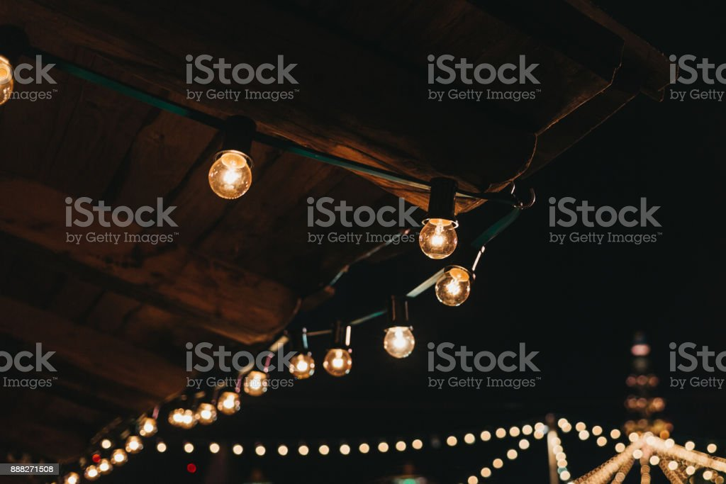 The string of vintage lights bulbs outside at night stock photo