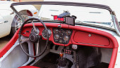 Athens, Georgia - July 01, 2017: The stripped-down cockpit of a red and white vintage Triumph Roadster TR3 on display at the monthly gathering of classic car enthusiasts called Cars & Coffee.