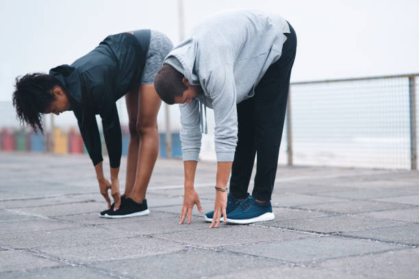 The stronger you get, the more flexible you'll become too Shot of two sporty young people stretching while exercising outdoors touching toes stock pictures, royalty-free photos & images