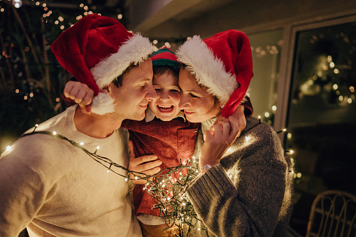 Photo of a family with one child wrapped in Christmas lights,  celebrating holidays on the balcony of their apartment; throwing an unforgettable Christmas party at home.