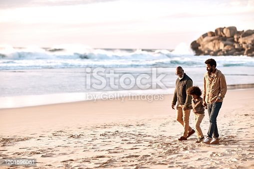 Shot of an adorable little boy going for a walk along the beach with his grandfather and father