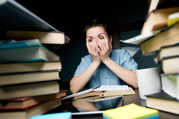 La estudiante mira cansadamente a través de sus dedos en la montaña de los libros - foto de stock