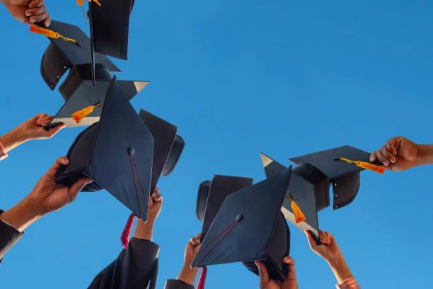 los estudiantes que sostienen una foto de la gorra de graduación por su mano en un cielo brillante durante la ceremonia de éxito graduados en la universidad, concepto de educación exitosa en la escuela secundaria, grado de felicitación - graduación fotografías e imágenes de stock