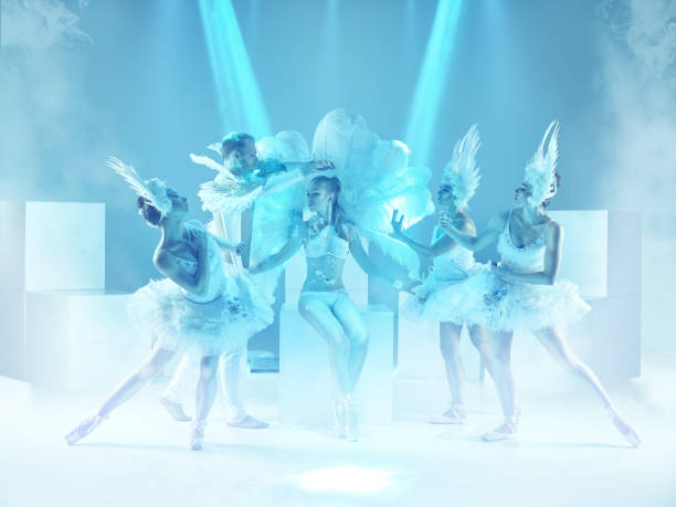 the studio shot of group of modern dancers on blue background - dance group stock photos and pictures
