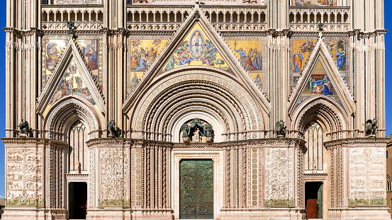 A detailed front view of the stunning Gothic facade of the Basilica of Santa Maria Assunta or Duomo in the medieval town of Orvieto, in the Umbria region, central Italy. The construction of the magnificent Duomo, a masterpiece of Italian Gothic art, began in 1290 under the pontificate of Pope Nicholas IV and was completed in the second half of the 15th century. More than 20 artists worked on the magnificent façade of the Cathedral during the two centuries of construction of the church. With a population of just 20,000 people, Orvieto is considered one of the most beautiful cities of art in Italy, founded since the Etruscan and Roman times on the flat top of a large butte of volcanic tuff. This same material was used for the construction of almost all the medieval houses and churches of Orvieto, as well as its famous Gothic-style Cathedral. Image in high definition format.