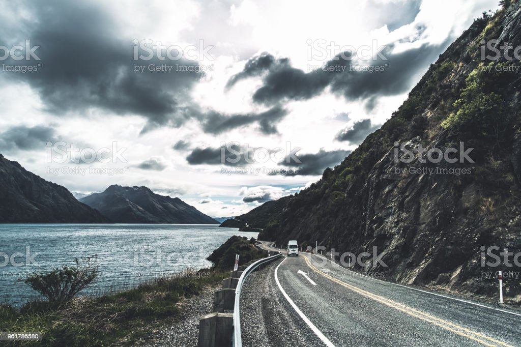 The stunning landscape of road beside the ocean with a cloudy and mountain scene. royalty-free stock photo
