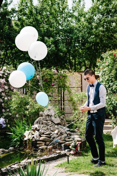 der stilvolle bräutigam trägt luftballons am brunnen im innenhof. ein mann bereitet sich auf eine hochzeitsfeier vor. hochzeit morgen, natur. close up - pier 1 dekor stock-fotos und bilder