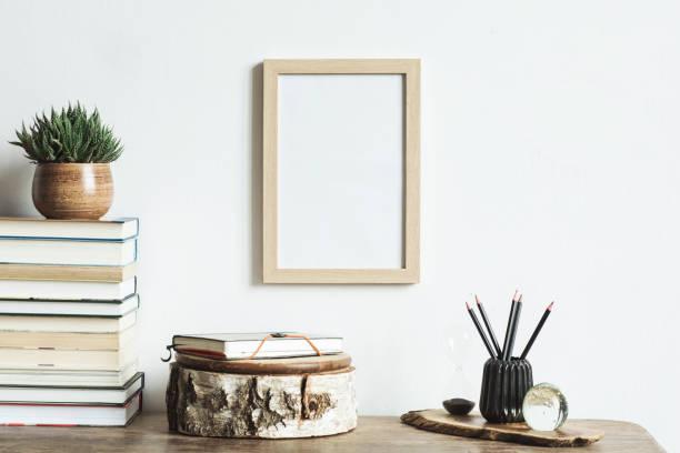 das stilvolle interieur mit mock-up posterrahmen, pflanzen, bücher und notebook. das retro-konzept des raumes. - glasskulpturen stock-fotos und bilder
