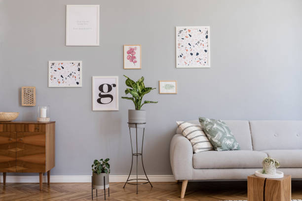 the stylish scandinavian interior of living room at nice apartment with gray sofa, deign wooden commode and cube, plants and elegant accessories. mock up posters gallery wall.modern home decor. - deign stock pictures, royalty-free photos & images