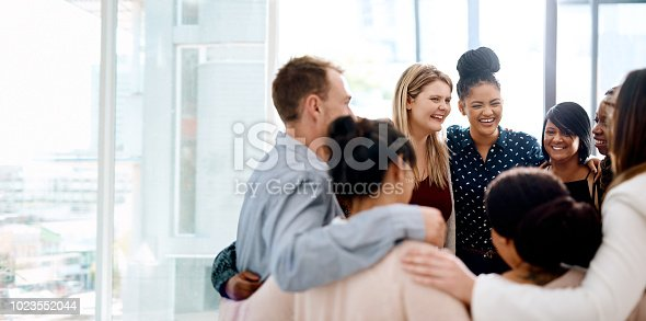 Shot of a group of young businesspeople huddled together in solidarity in a modern office