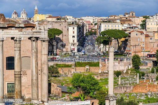 A suggestive image of the Imperial Forums, an area known as the Archaeological Park of the Roman Forum, taken from the Capitoline Hill. In the foreground on the left the majestic columns of the ancient Temple of Saturn, while Viale dei Fori Imperiali and the Monti district can be seen. The Roman Forum is one of the largest archaeological areas in the world. Image in high definition format.