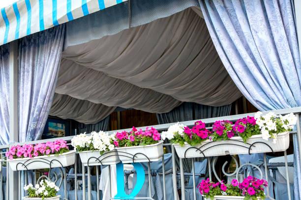 die sommerterrasse des restaurants befindet sich eine überdachte pergola mit vorhängen eingerichtet und in hellen farben mit blumentöpfe für blumen drapiert. - garagen pergola stock-fotos und bilder