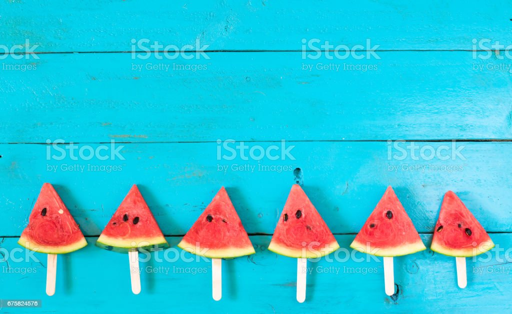 the summer watermelon slice popsicles on a blue rustic wood background. copy space for designer stock photo