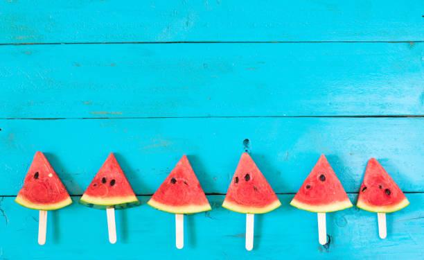 the summer watermelon slice popsicles on a blue rustic wood background. copy space for designer - foto de acervo