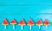 the summer watermelon slice popsicles on a blue rustic wood background. copy space for designer
