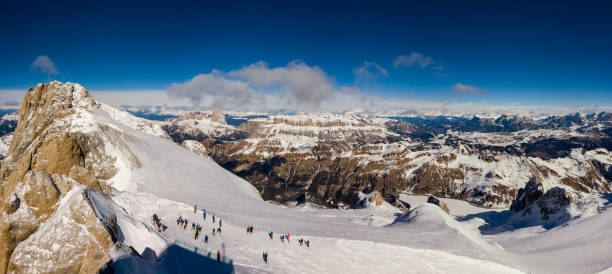 The summit of Marmolada with skiers getting ready and Mount Sella on the background on a beautiful sunny day, Dolomites, Italy Panorama from the summit of Marmolada with skiers getting ready and Mount Sella on the background on a beautiful sunny day, Dolomites, Italy trentino alto adige stock pictures, royalty-free photos & images