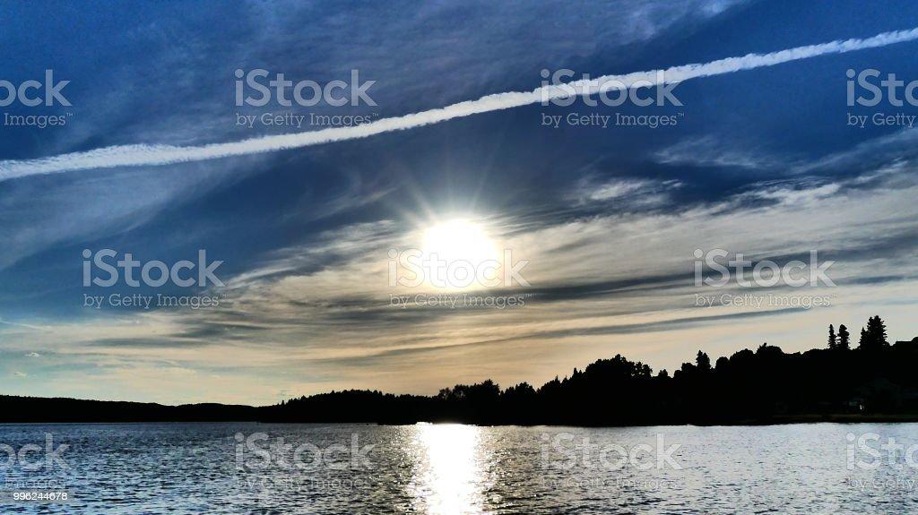 Le soleil et son halo lumineux sur l'eau avec une trace blanche d'avion dans le ciel stock photo