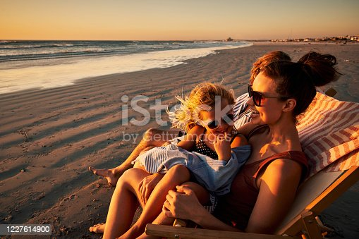Shot of an adorable little girl relaxing on a chair at the beach with her mother