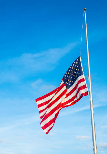 the Sun comes out after mass shooting American Flag at Half Mast after another School Shooting stock photo