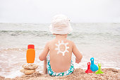 The sun drawing sunscreen (suntan lotion) on baby (boy)  back. Caucasian child is sitting with plastic container of sunscreen and toys on sunny beach. Close up, outdoor, copyspace (Sharm El Sheikh, Egypt).
