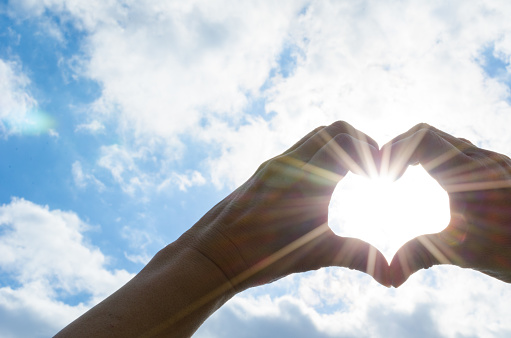 istock The sun in heart shaped hands 1220511562