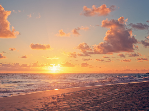 Sunrise over the sea or the ocean. Above the sandy beach is the morning sky with clouds.