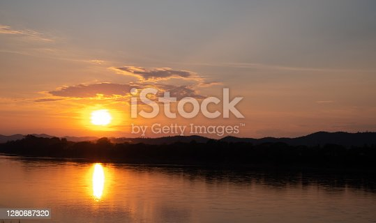 The sun is falling behind the mountain view the beautiful river and overcast sky cloud