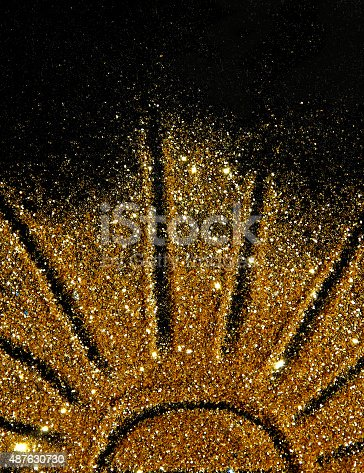 The sun of golden glitter sparkle on black background