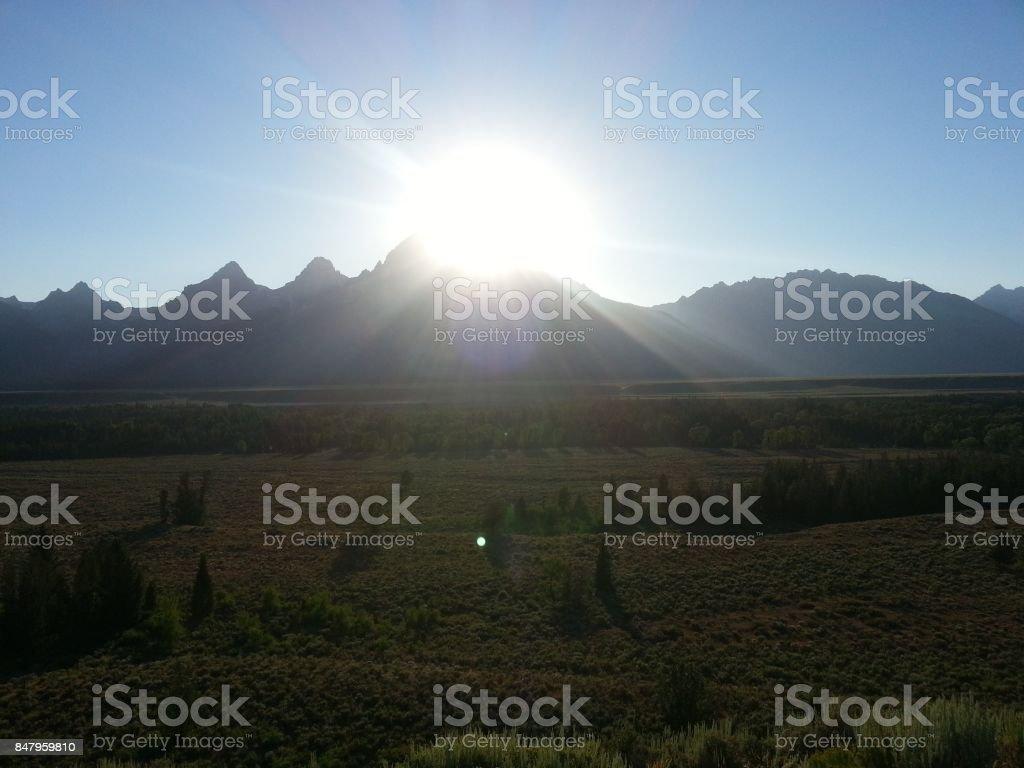 The Sun Pierces the Mighty Tetons stock photo