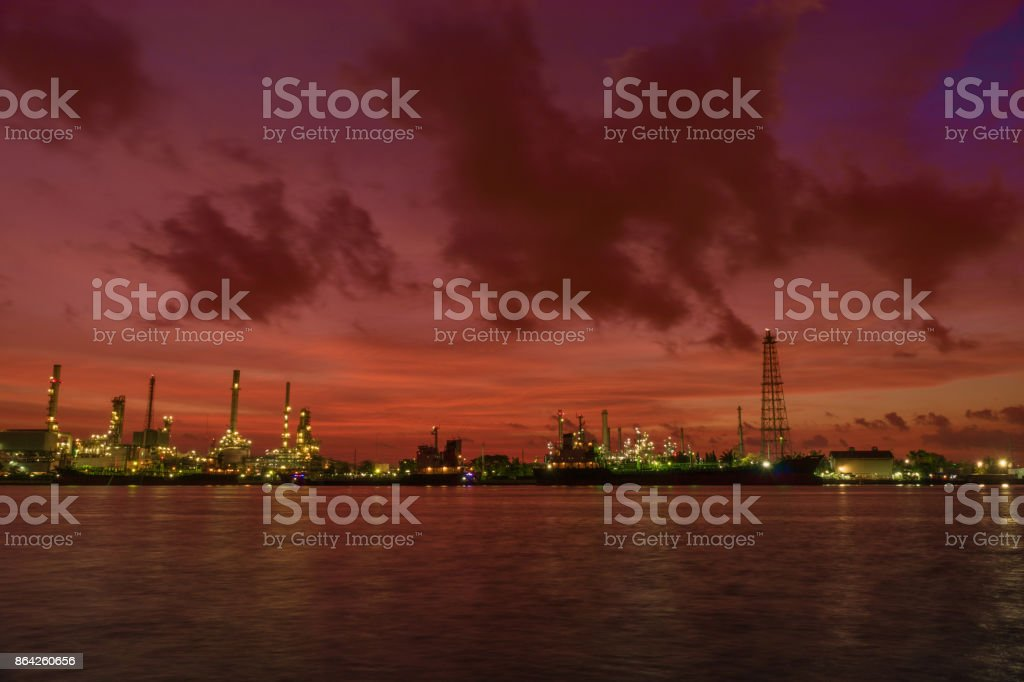 The sun rises in the morning with oil station Bangchak Petroleum's oil refinery, beside the Chao Phraya River, Bangkok, Thailand royalty-free stock photo