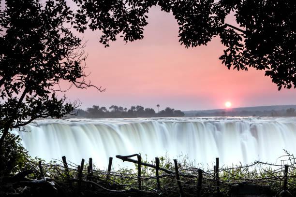die sonne geht über victoria falls, simbabwe, auf. - fluss sambesi stock-fotos und bilder
