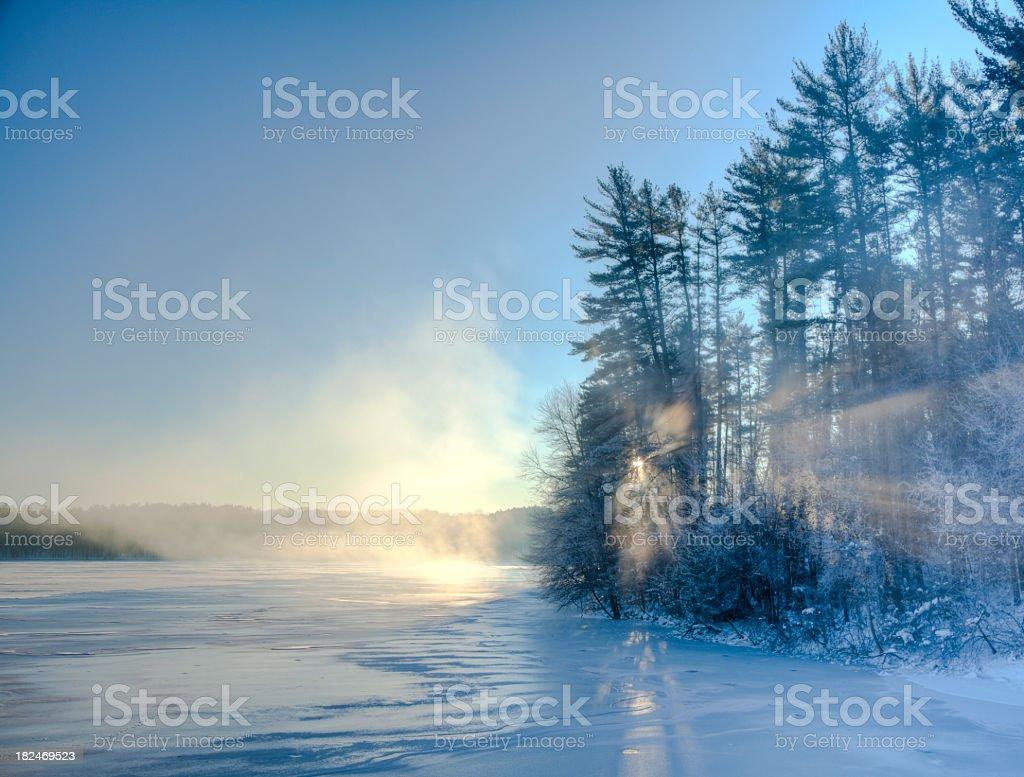 The sun rising over a winter landscape stock photo