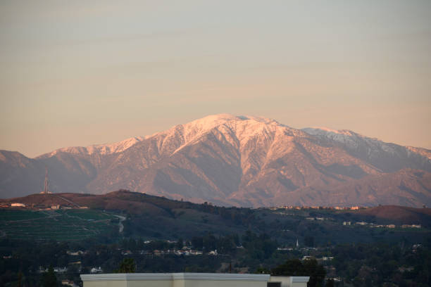 The Sun Sets on California's Mt. Baldy A snapshot of the snow-covered summit of Mt. Baldy as the sunset gives it an orange hue during golden hour. mount baldy stock pictures, royalty-free photos & images
