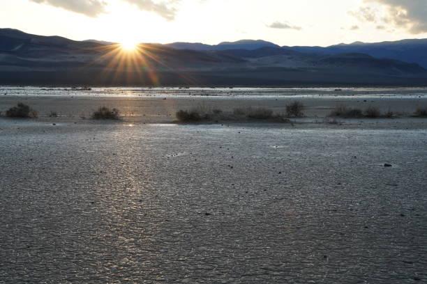 The sun sets over a desert playa stock photo