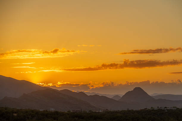 The sun setting behind mountains in the Sonoran Desert stock photo