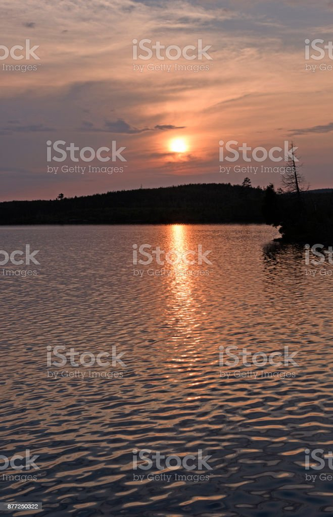 The Sun Setting Through Evening Clouds stock photo