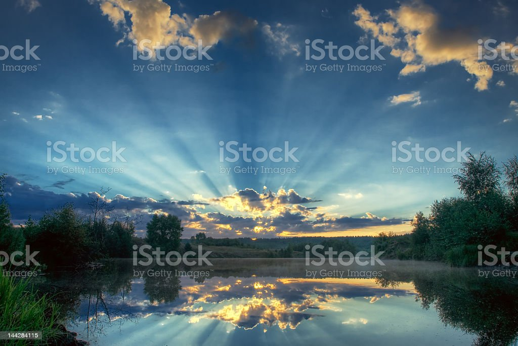 The sun setting through fluffy clouds stock photo