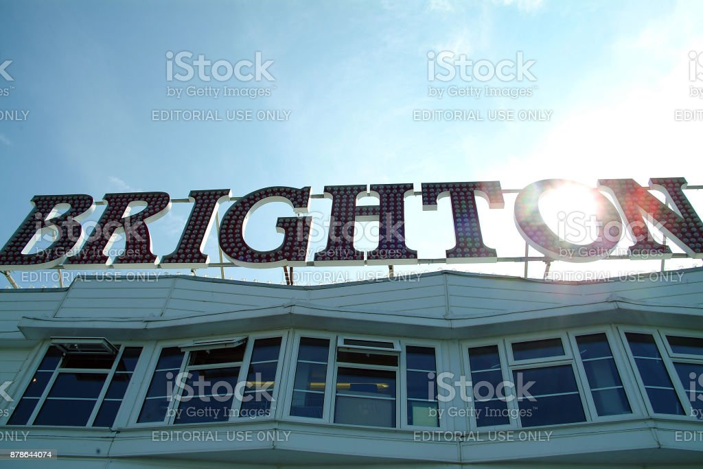 The Sun shining thrrough the Brighton signe on brighton's world famous pier stock photo