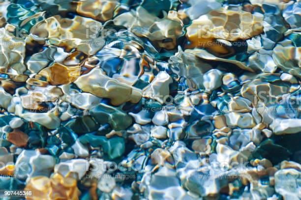 Photo of The sun shone through the stream on the pebbles.