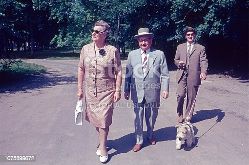 Hamburg, Germany, 1963. Hamburg couple on a Sunday walk, accompanied by a friend with a dog.
