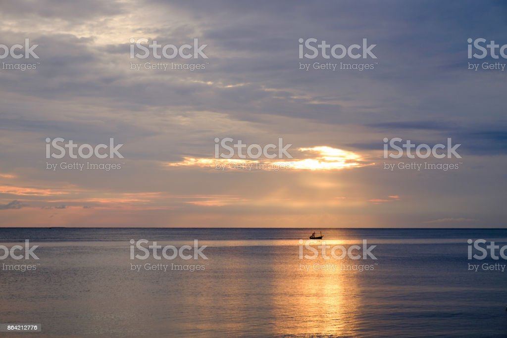 The sunrise at the seaside, in the days of the invisible Sun and a boat under the sun royalty-free stock photo