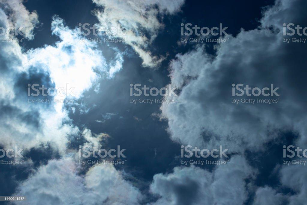 The sun\'s rays make their way through the storm clouds. Dark rain...