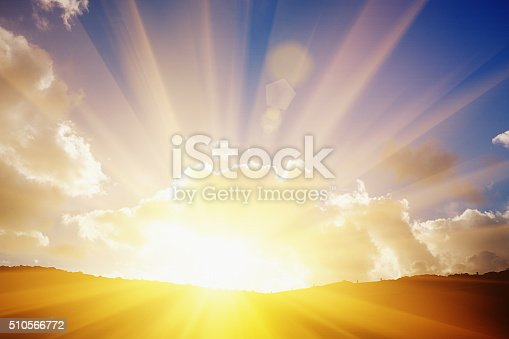The sun breaks through clouds as it rises - or sets - on the horizon, creating dramatic lens flare. As the saying goes, every cloud has a silver lining.
